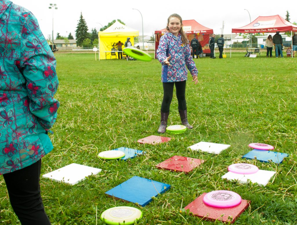 "A carnival-goer plays Frisbee tic-tac-toe, one of the Carnival of Hope games. The rain didn't stop people from coming out, organizer Brenda Baumeister said. ""Kids were out there in their little mud suits. It was great."""