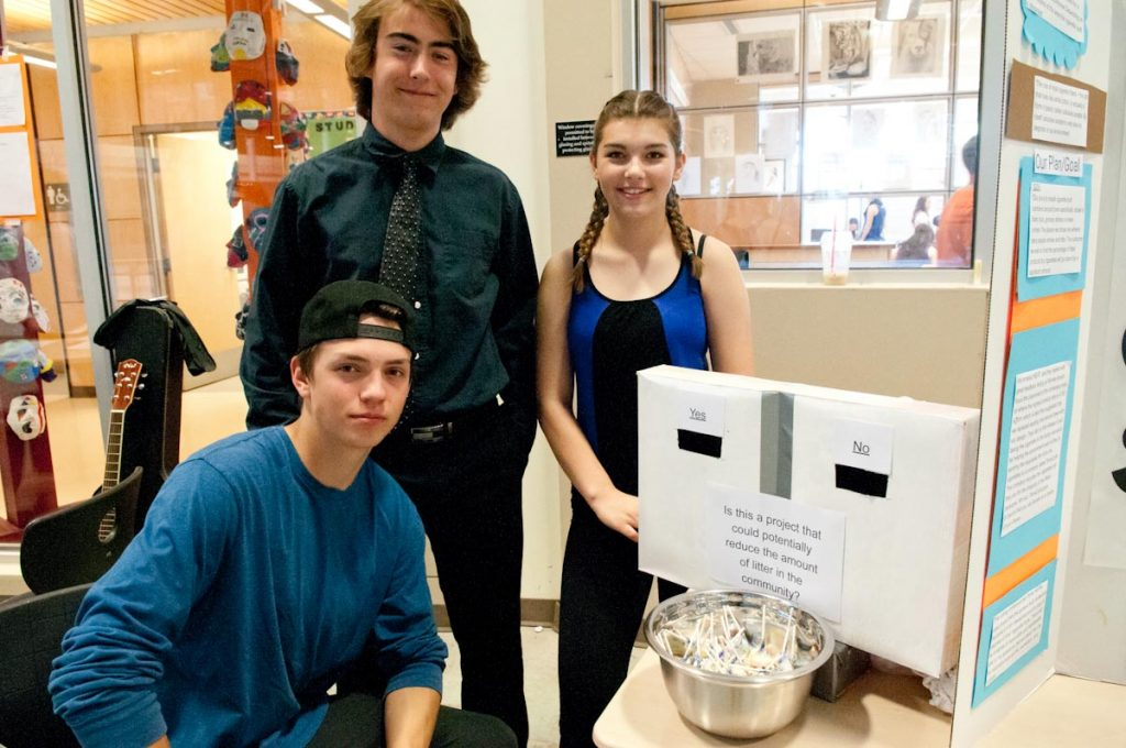 "Energetic Learning Campus students Jayden Piket, Reid Jacobs, and Rachelle Mackey have noticed a lot of cigarette butts on the ground. They've come up with a new disposal unit that polls smokers on fun questions—such as ""Messi v. Ronaldo""—by having them drop butts into a container with a centre partition. A plexiglass front lets everyone see the results of the poll, and questions can be changed periodically."